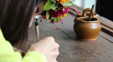 girl wearing a garland writing a postcard by a window