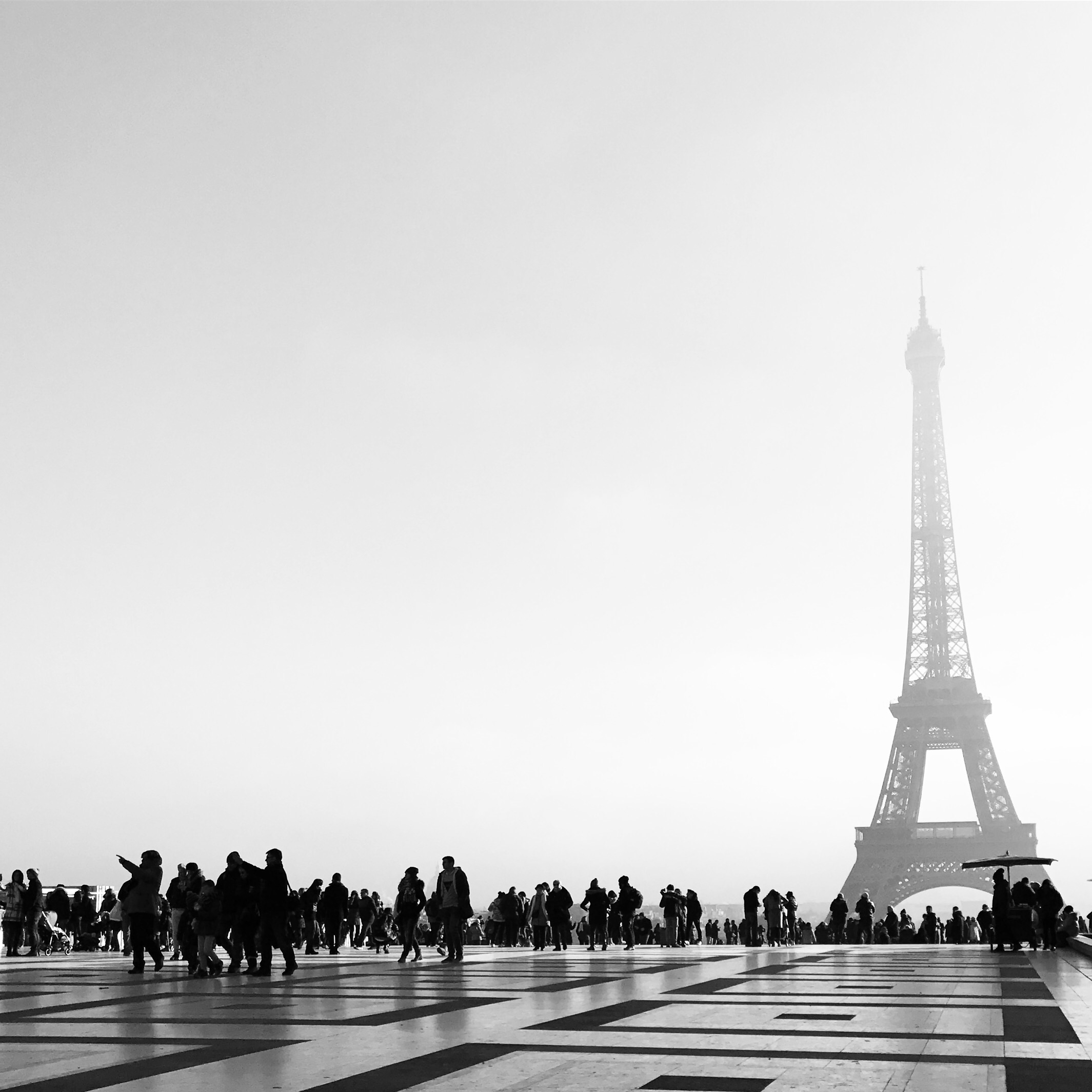 Photo of the Effiel Tower in the distance and people milling about a square in the foreground