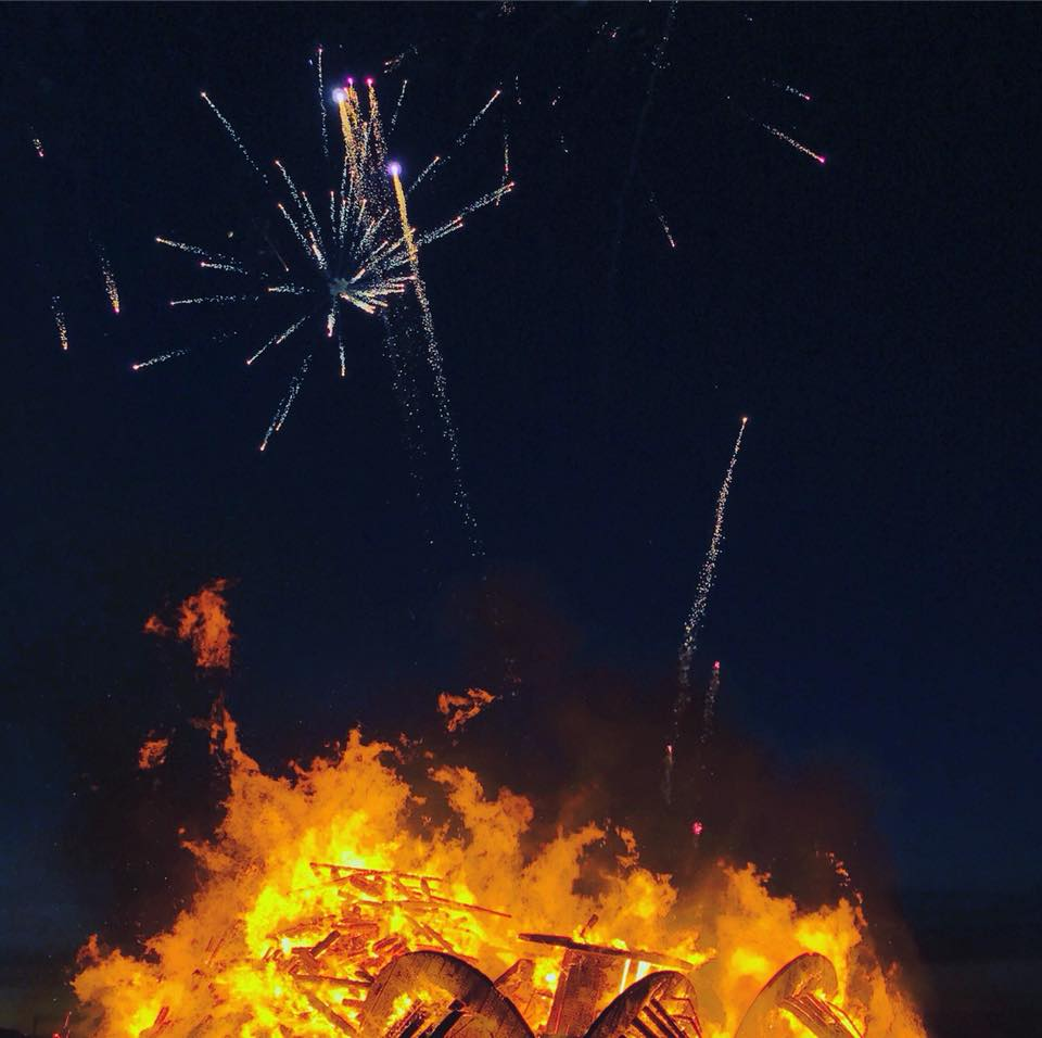 Photo of fireworks over a bonfire