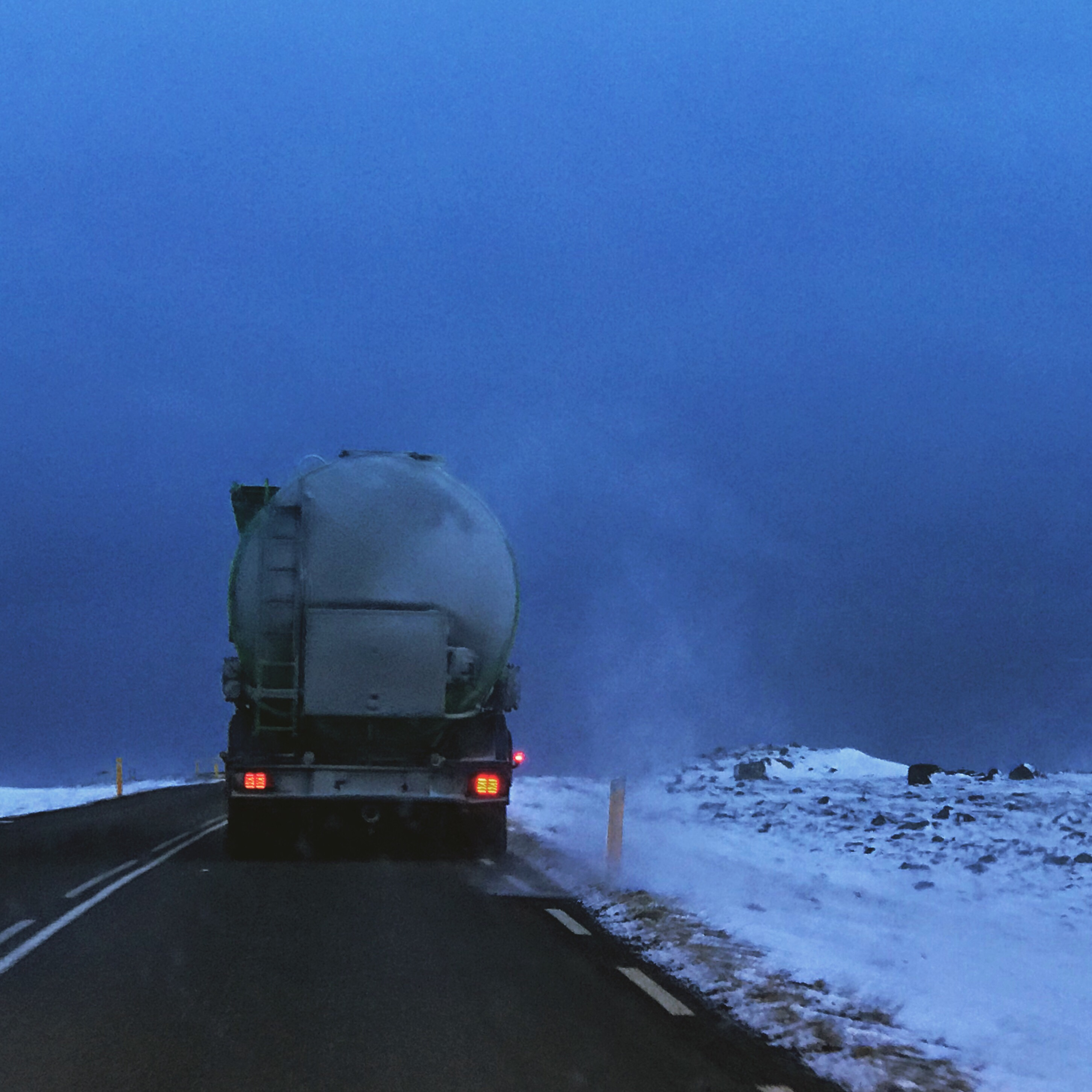 Photo of a truck driving through a snow storm