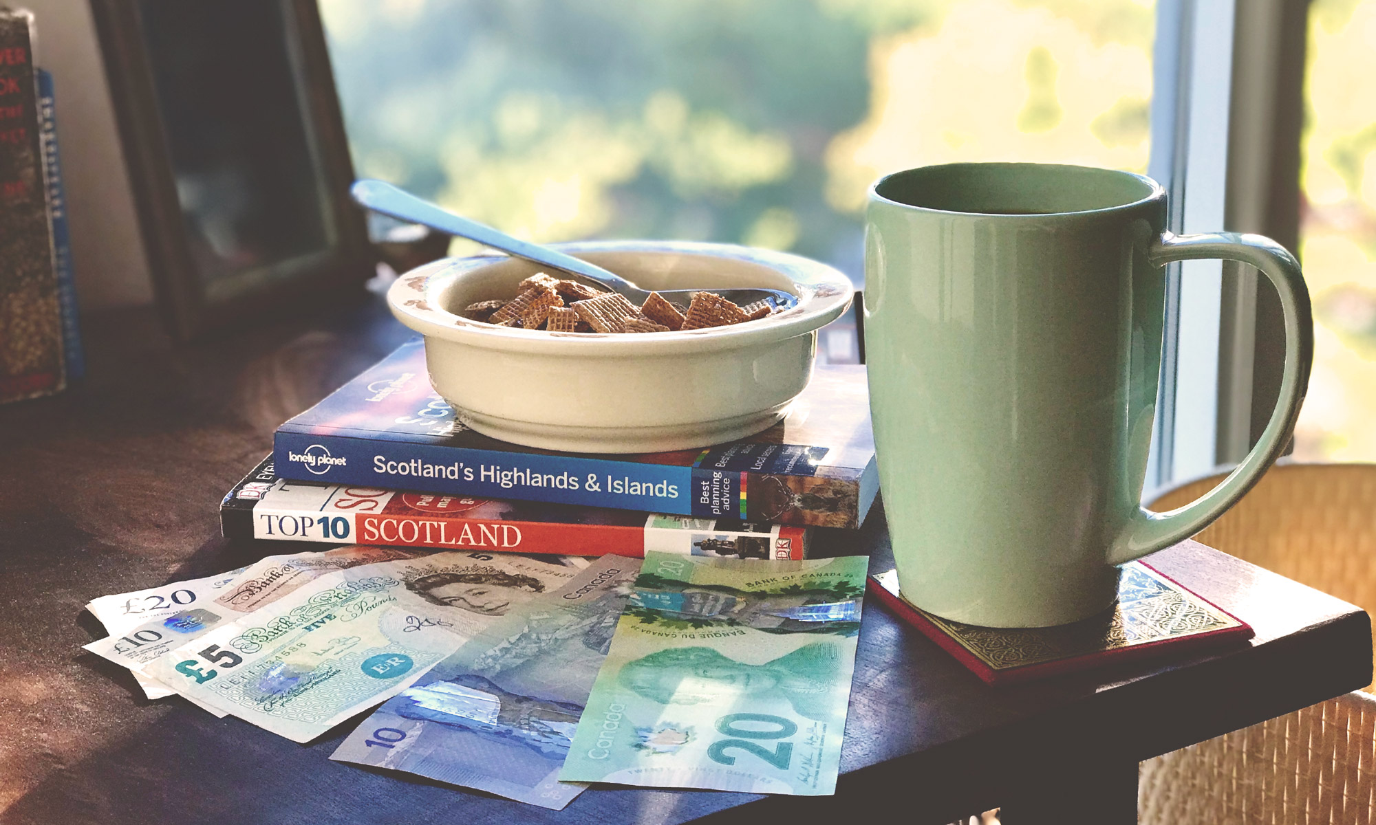 Photo of British and Canadian money next to two travel books on Scotland, a mug and cereal bowl