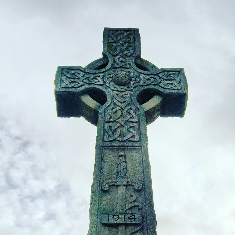 Photo of a stone Celtic Cross against the clouds