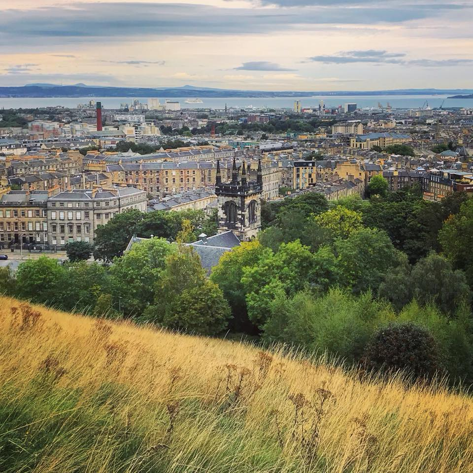 Photo of grass, trees, a church steeple and Edinburgh seen from above