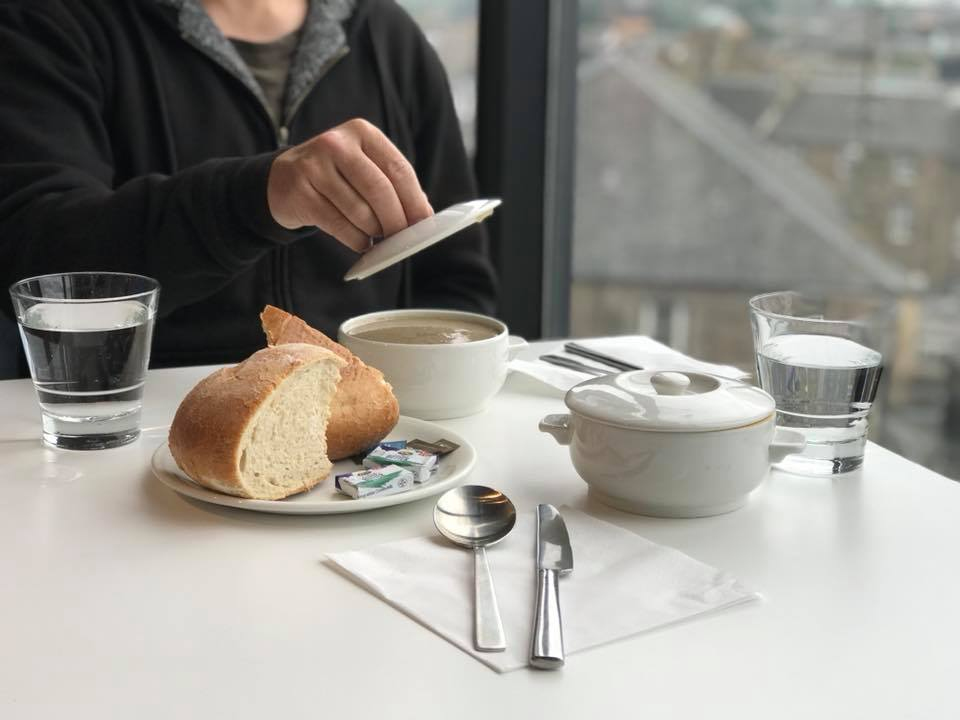 Photo of a man lifting a lid off a bowl of soup next to thick slices of bread