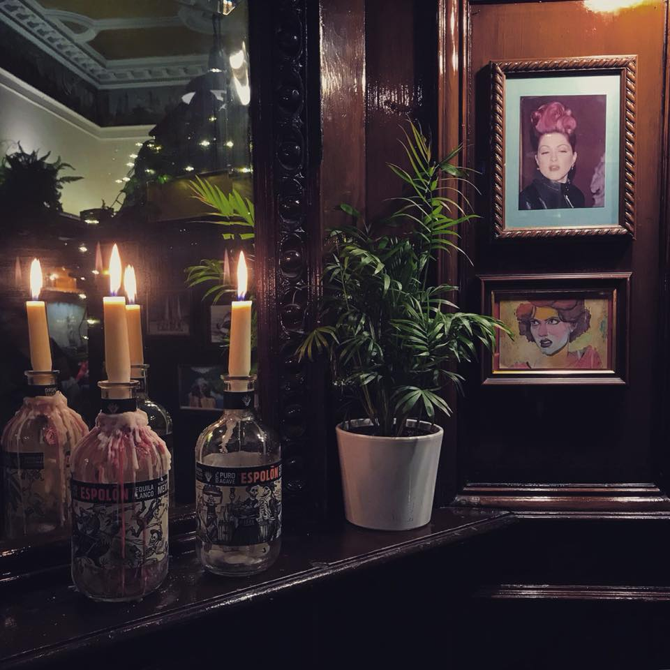 Photo of two candles in liquor bottles on a mantel with two photos of scowling women on the walls