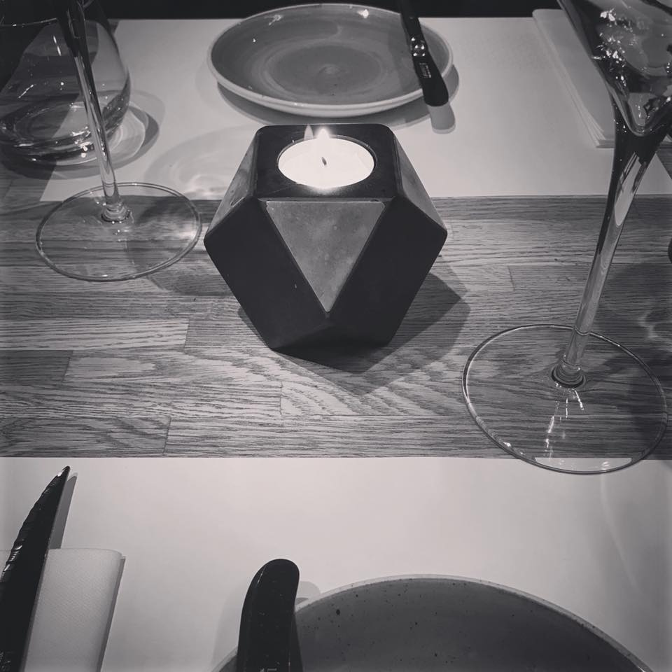 Photo of a table set for two with a geometric candle holder in the middle